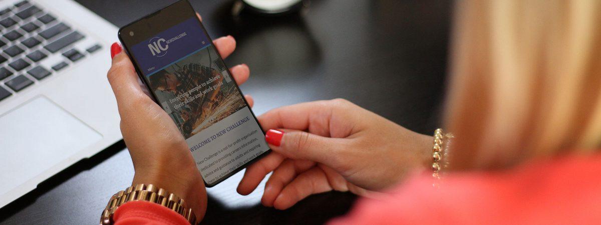 Woman viewing New Challenge website on her smartphone